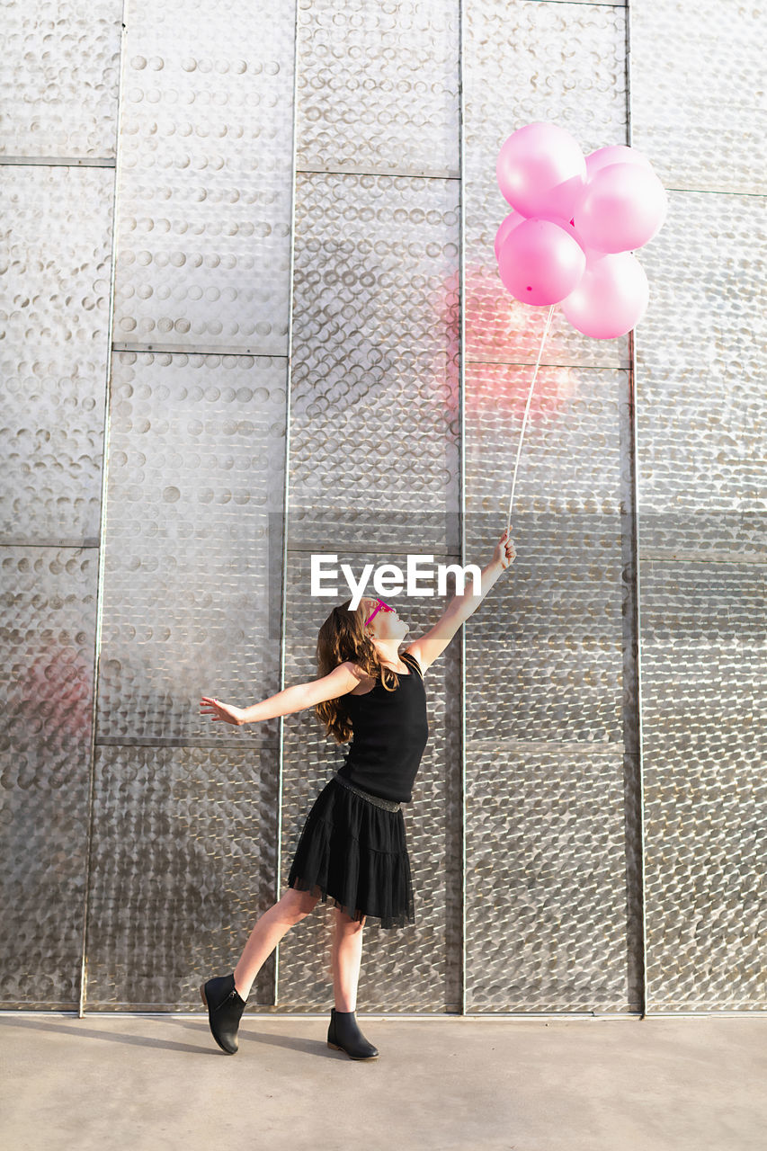 FULL LENGTH OF WOMAN WITH PINK BALLOONS AGAINST WALL