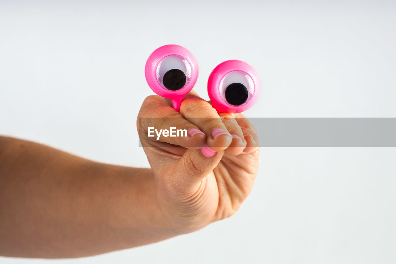 human hand, hand, human body part, one person, holding, studio shot, indoors, pink color, white background, body part, close-up, personal perspective, finger, circle, lifestyles, human finger, real people, geometric shape, shape, human limb, nail