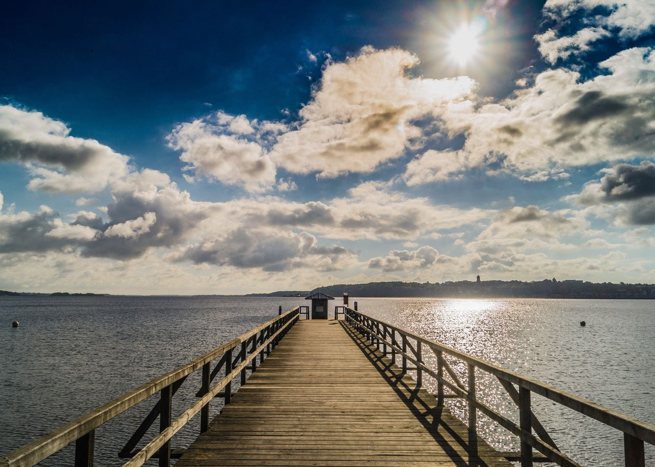 sky, water, cloud - sky, scenics - nature, pier, beauty in nature, sea, tranquility, nature, direction, the way forward, tranquil scene, sunlight, wood - material, built structure, railing, idyllic, architecture, horizon over water, outdoors, sun, no people, diminishing perspective, wood paneling, long