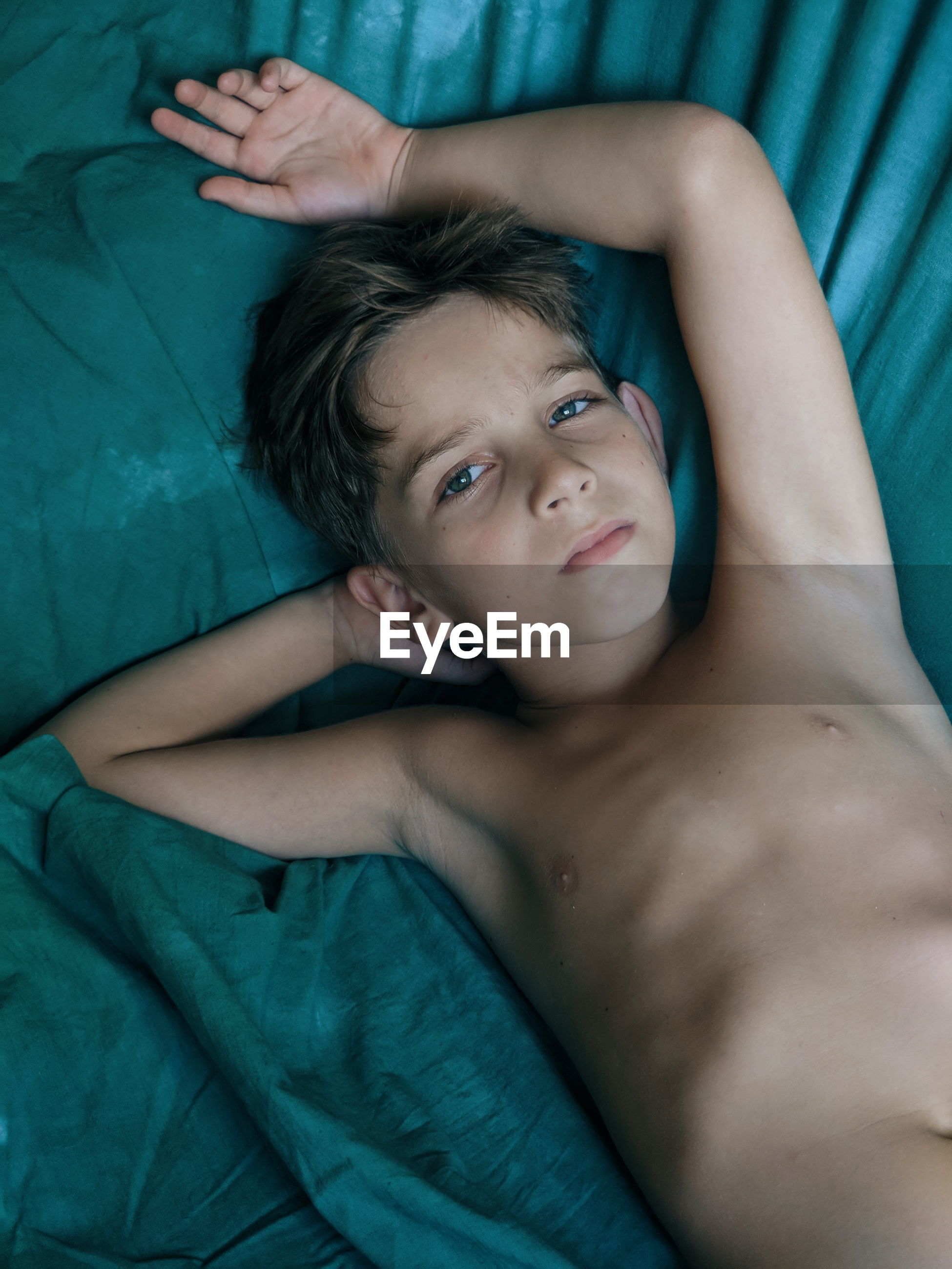 High angle portrait of shirtless boy lying on bed