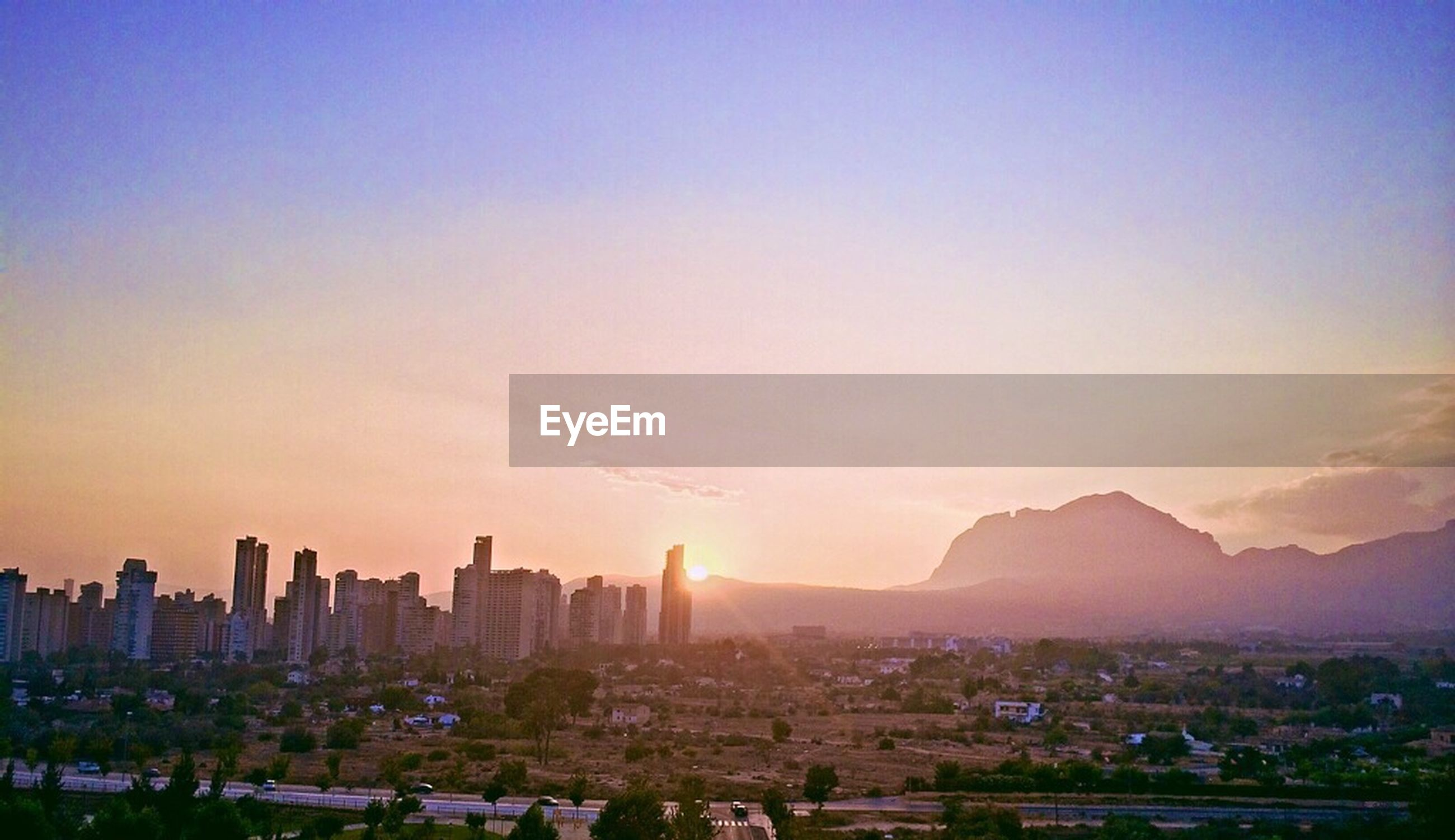 building exterior, cityscape, city, sunset, architecture, built structure, mountain, high angle view, sun, residential district, sky, crowded, silhouette, mountain range, scenics, copy space, sunlight, orange color, residential building, skyscraper