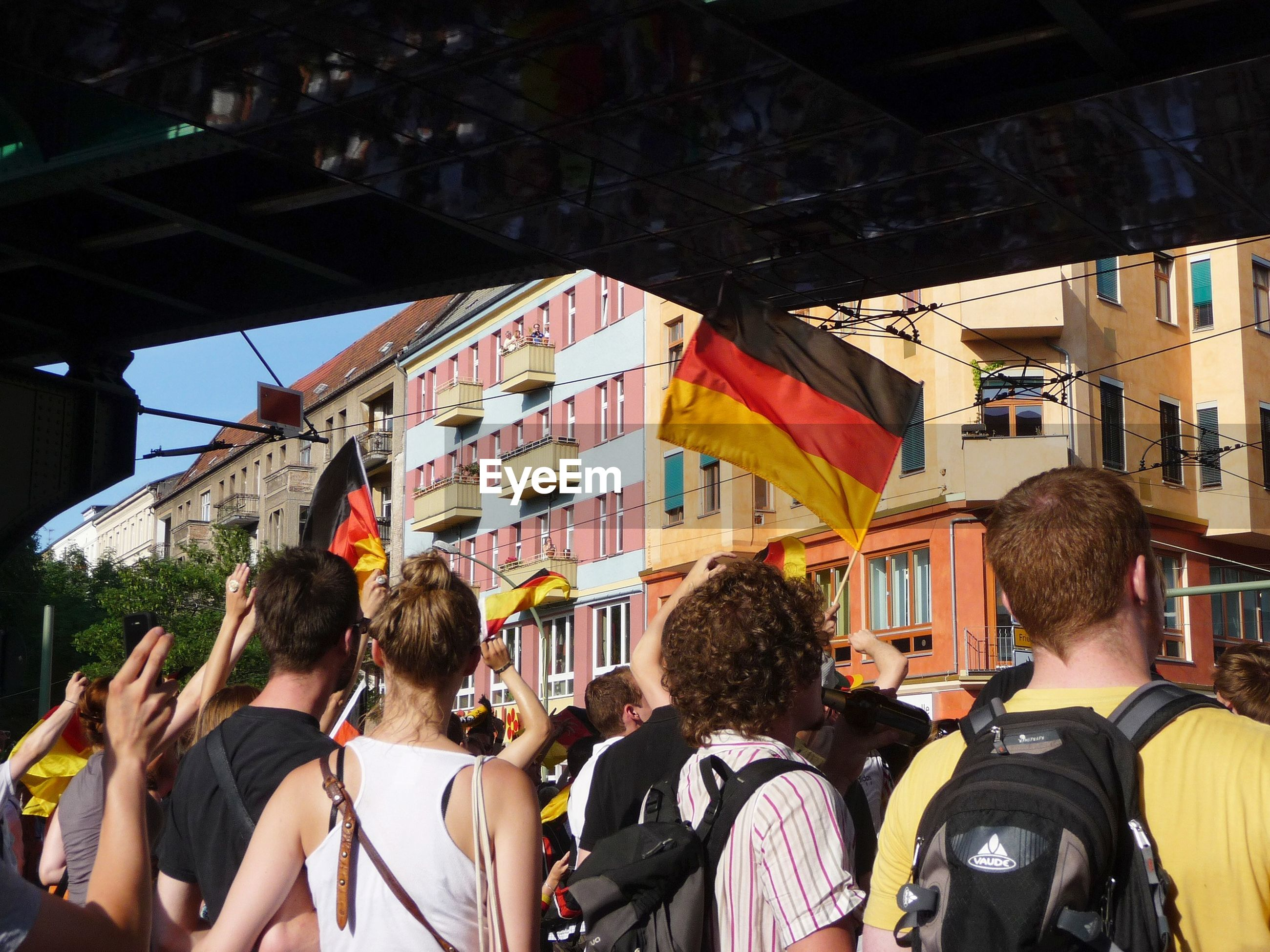 People on street holding german flag in city