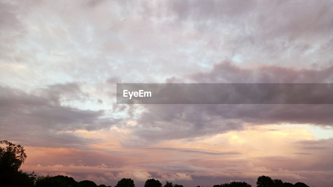 cloud - sky, sky, beauty in nature, nature, scenics, tranquility, tranquil scene, dramatic sky, sunset, weather, no people, idyllic, outdoors, low angle view, awe, storm cloud, tree, day