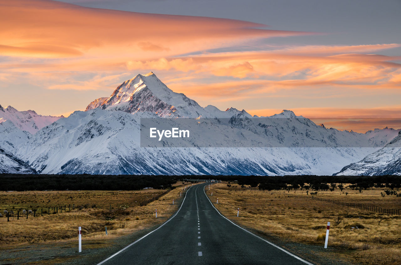Road By Snowcapped Mountains Against Sky During Sunset