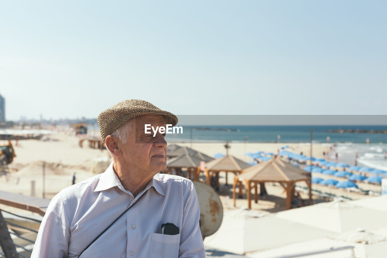 Close-up of senior man at beach against clear sky