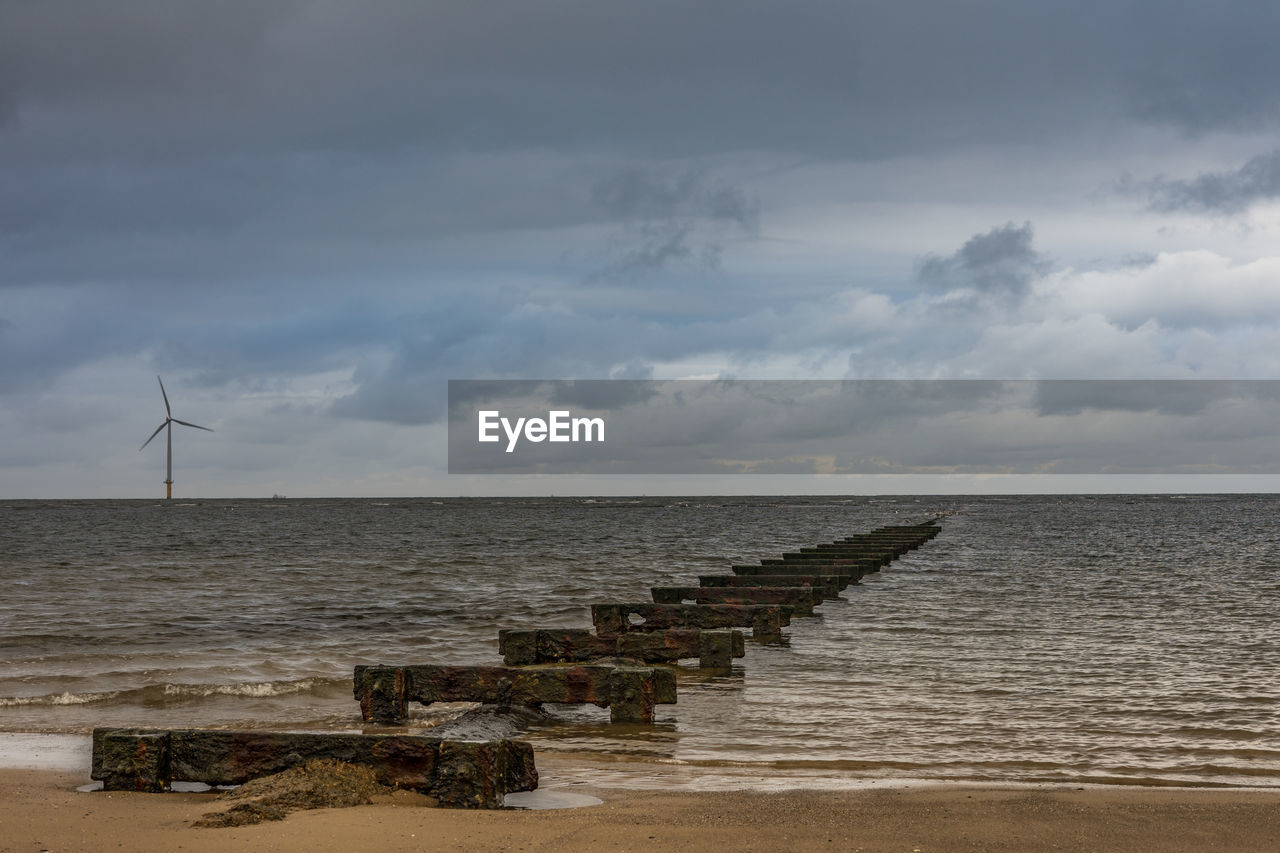 sky, water, sea, cloud - sky, horizon, horizon over water, beauty in nature, fuel and power generation, scenics - nature, tranquil scene, wind turbine, environment, land, tranquility, environmental conservation, renewable energy, nature, turbine, beach, no people, outdoors, groyne, power in nature
