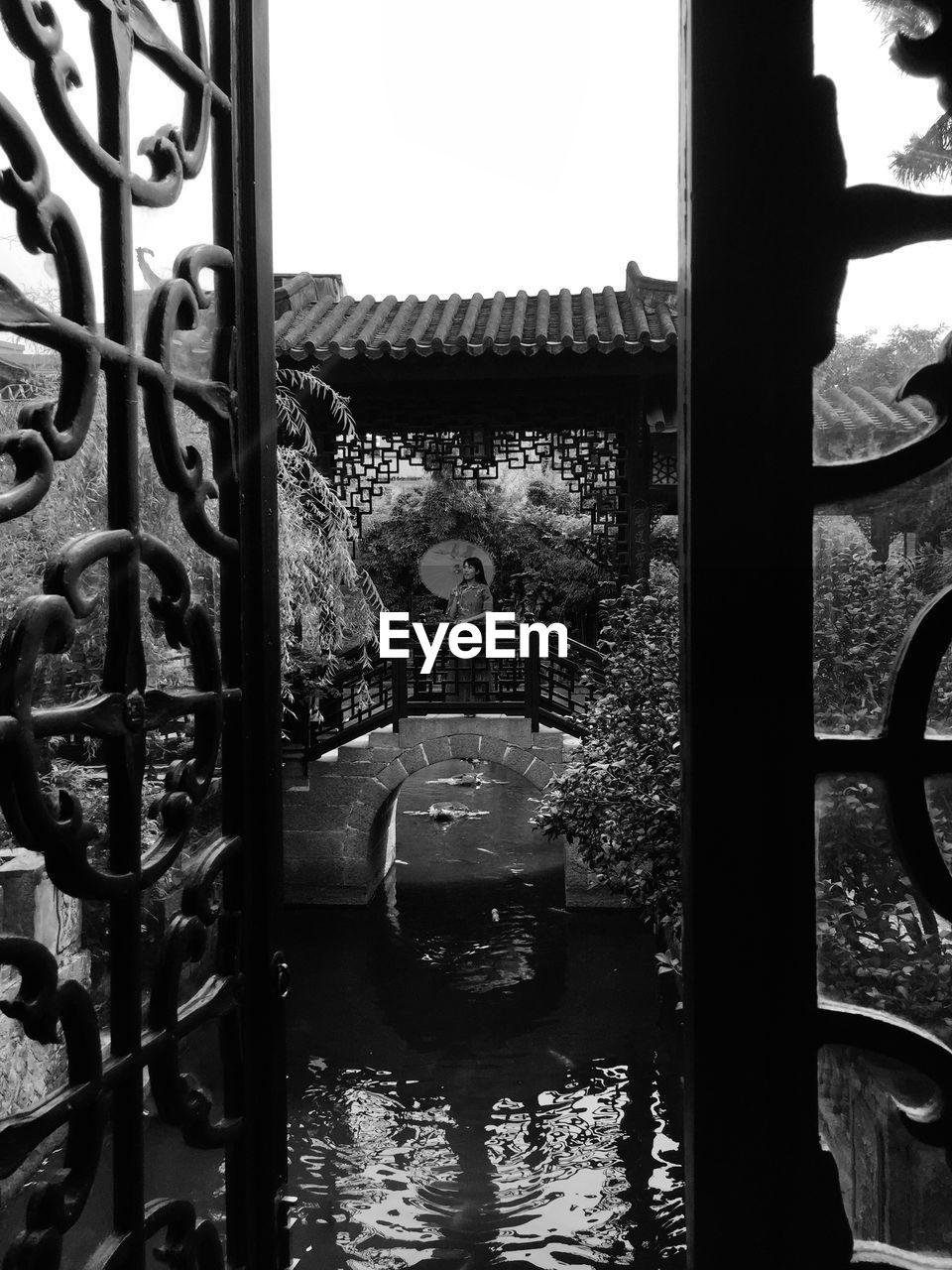 Woman Standing Holding Umbrella Under Roof Seen Through Metal Gate