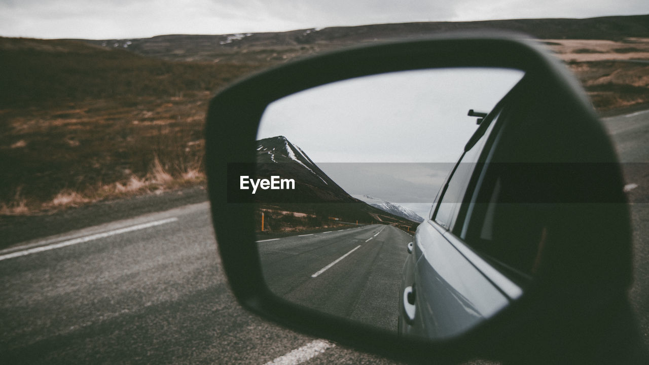 Reflection of road on side-view mirror of car
