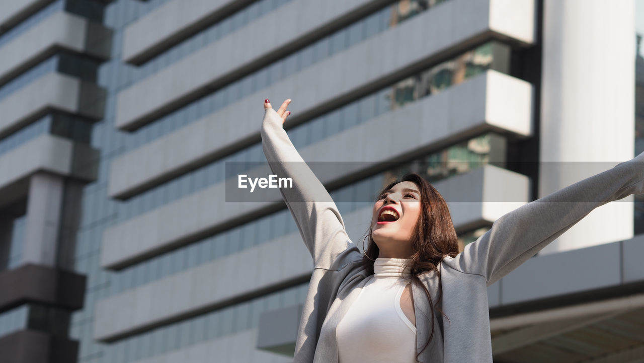 one person, mouth open, mouth, emotion, architecture, young adult, human arm, arms raised, building exterior, shouting, built structure, human body part, young women, real people, lifestyles, happiness, gesturing, leisure activity, front view, excitement