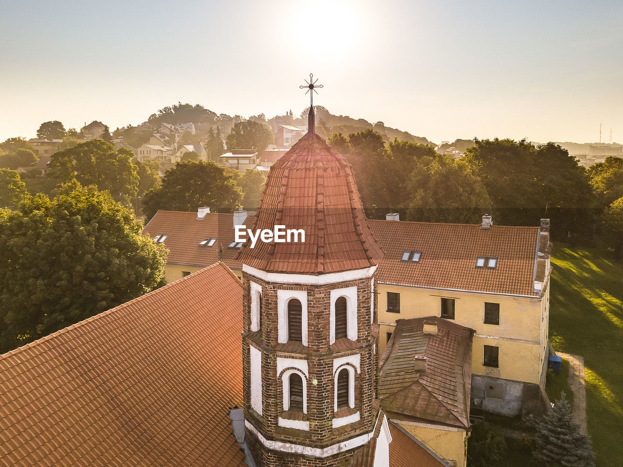 High Angle View Of Church Amidst Trees Against Clear Sky During Sunny Day