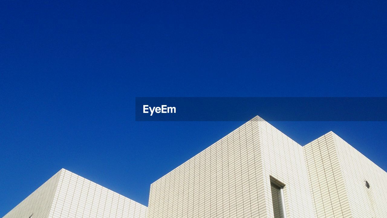 High section of building against clear blue sky