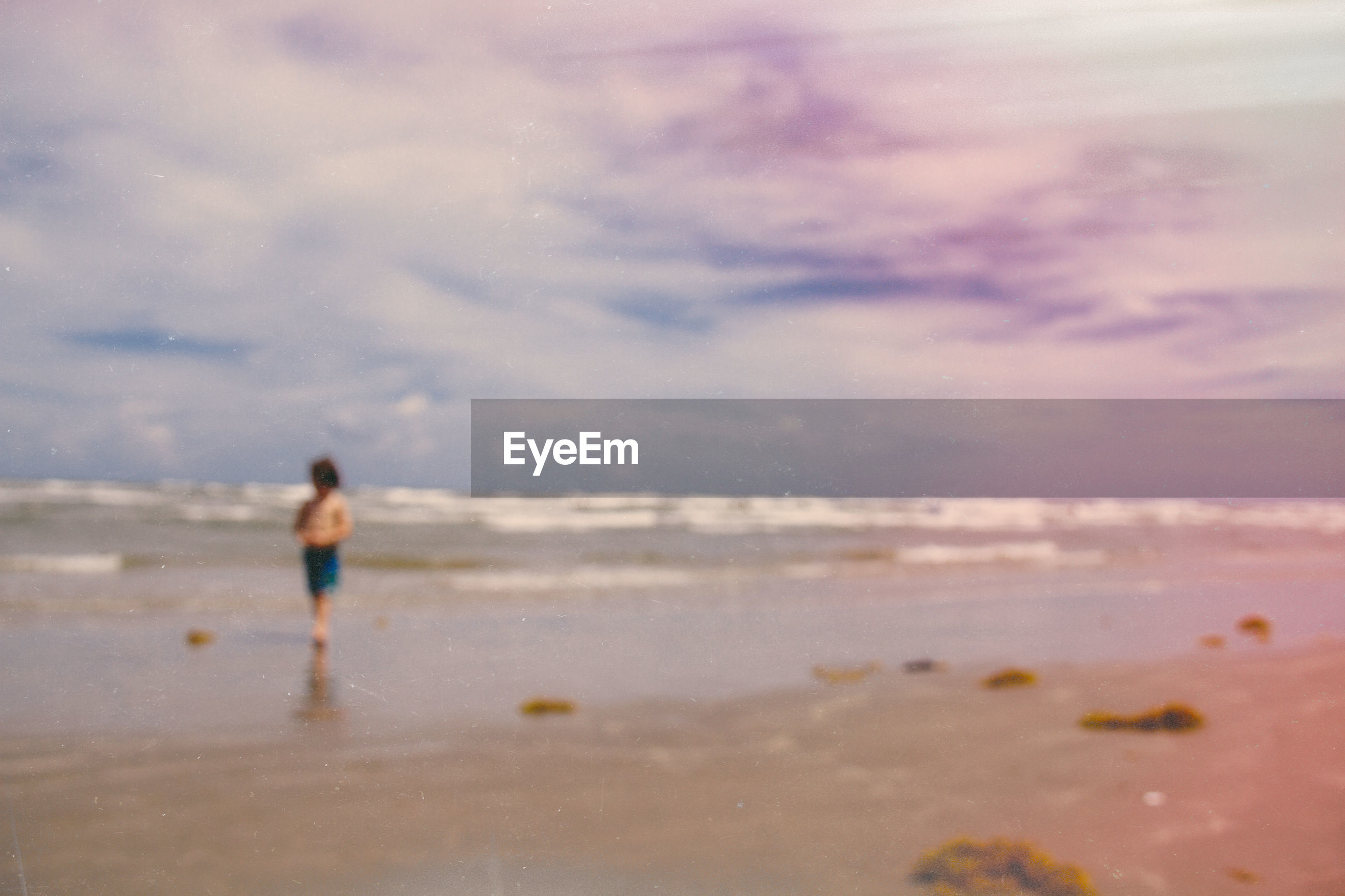 Defocused image of person walking on sea shore at beach during dusk