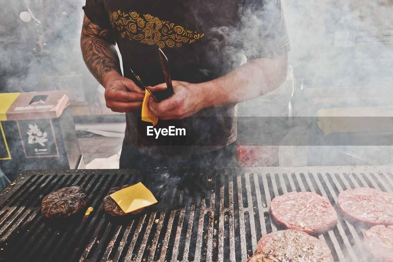 Men Cooking Hamburger On Barbecue