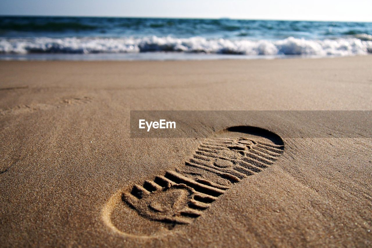 land, beach, sea, water, sand, nature, no people, motion, wave, day, art and craft, creativity, text, focus on foreground, horizon, footprint, horizon over water, tranquility, outdoors