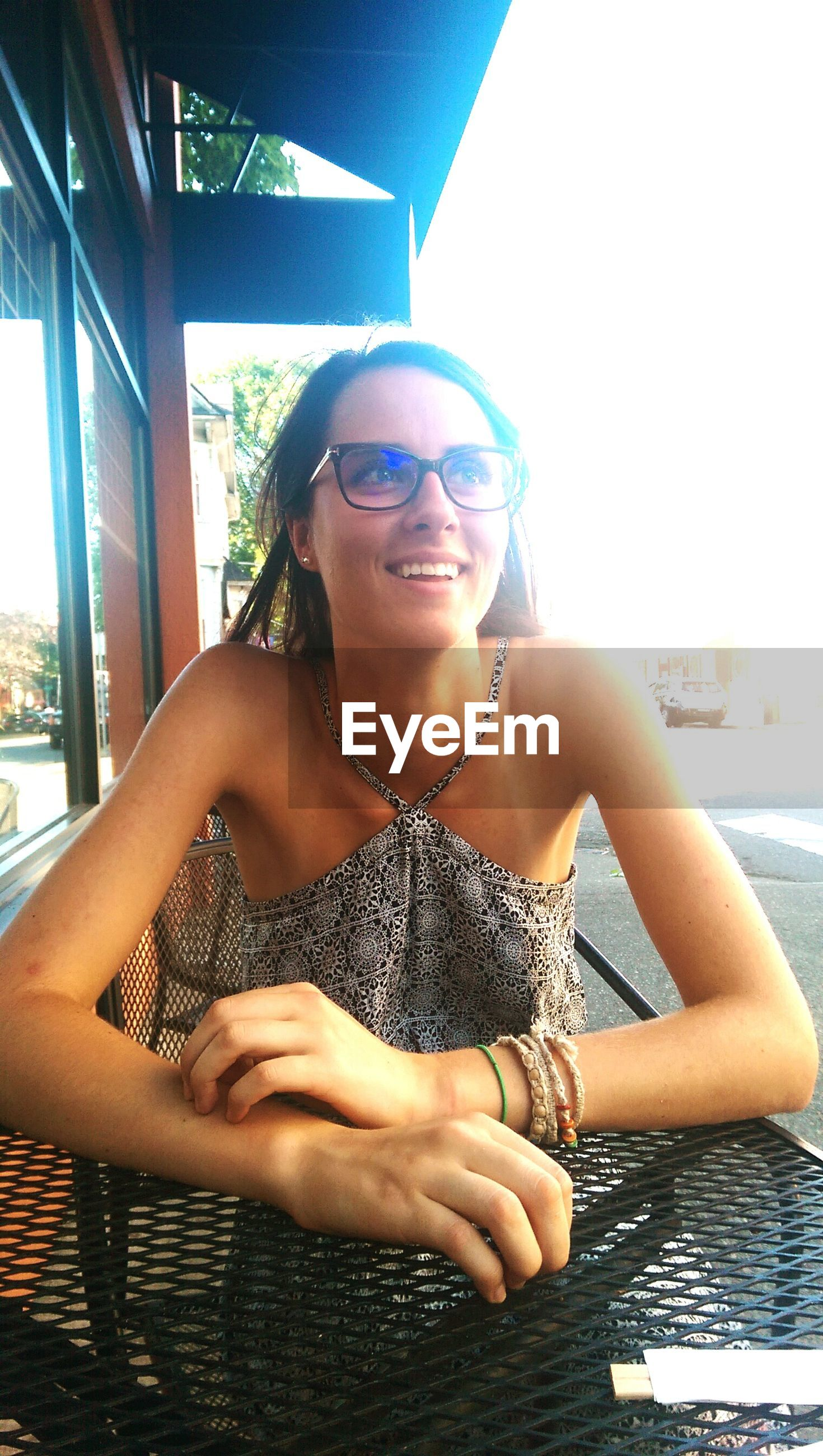 Happy young woman with eyeglasses sitting on chair
