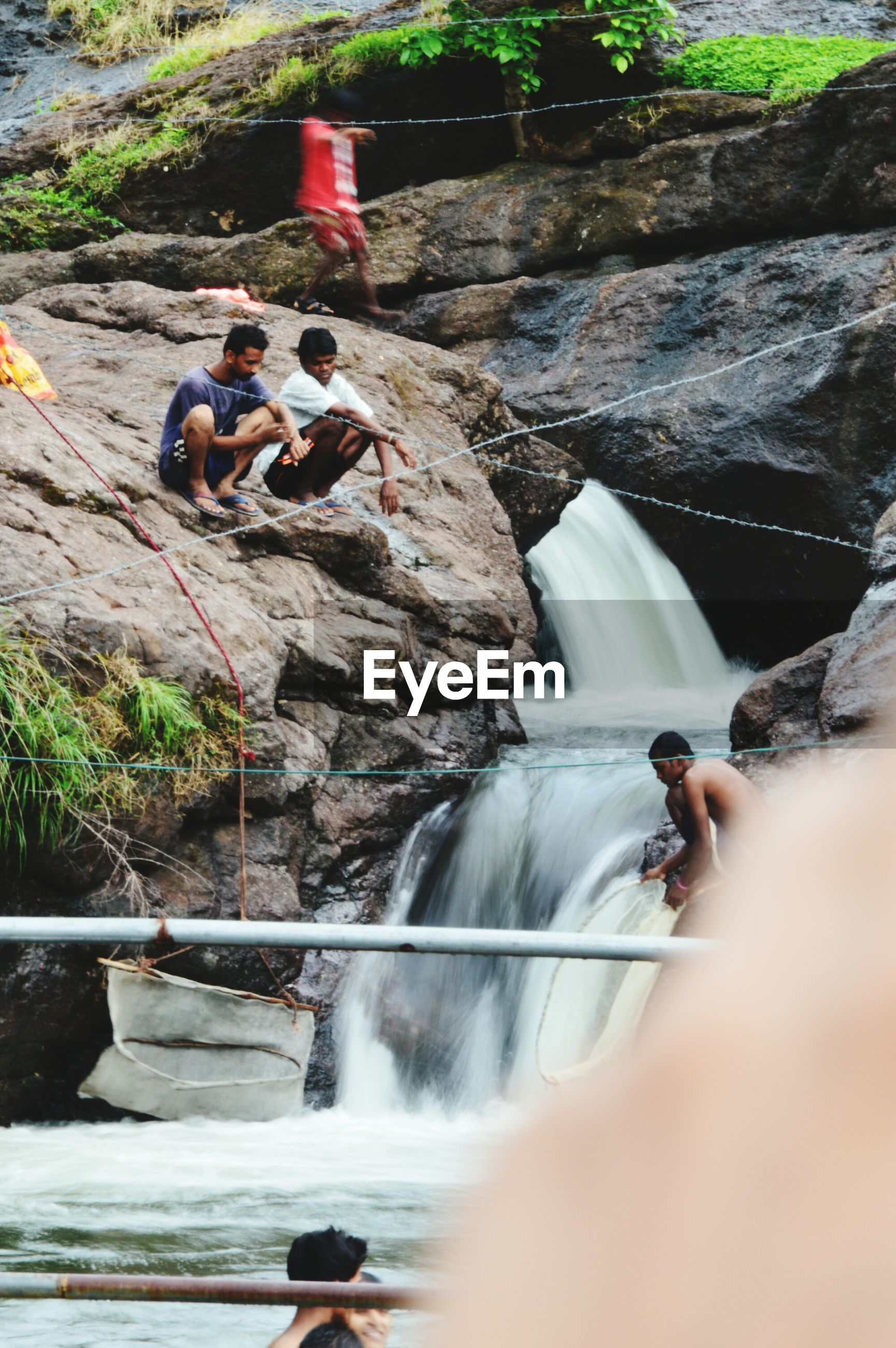 water, motion, waterfall, real people, day, rock - object, long exposure, river, outdoors, men, nature, beauty in nature, adventure, wooden raft, togetherness, human hand, people