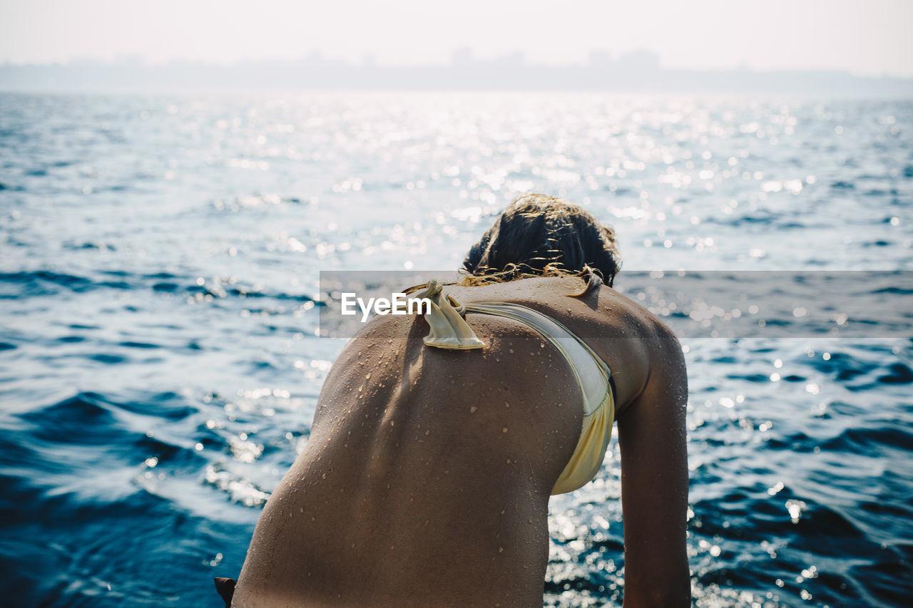 Rear view of young woman looking at sea shore