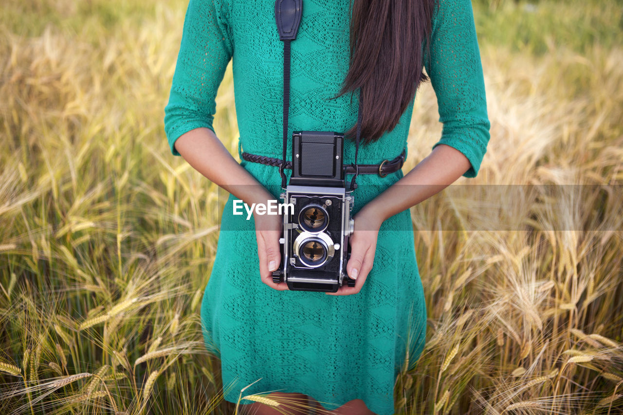 Midsection of woman photographing on field