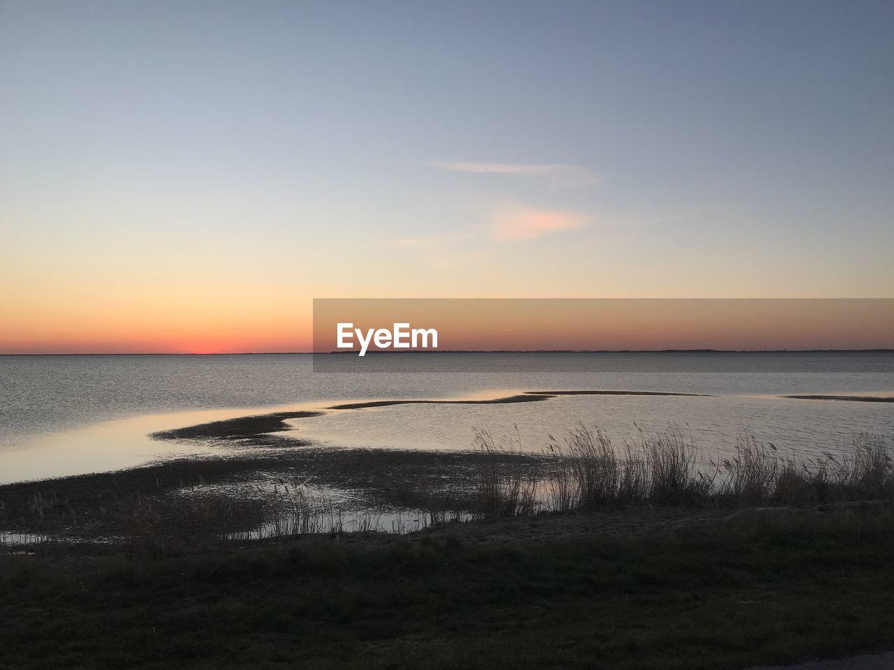 sky, water, scenics - nature, sunset, beauty in nature, tranquil scene, tranquility, sea, land, beach, horizon, horizon over water, idyllic, no people, nature, non-urban scene, orange color, grass, outdoors, marram grass
