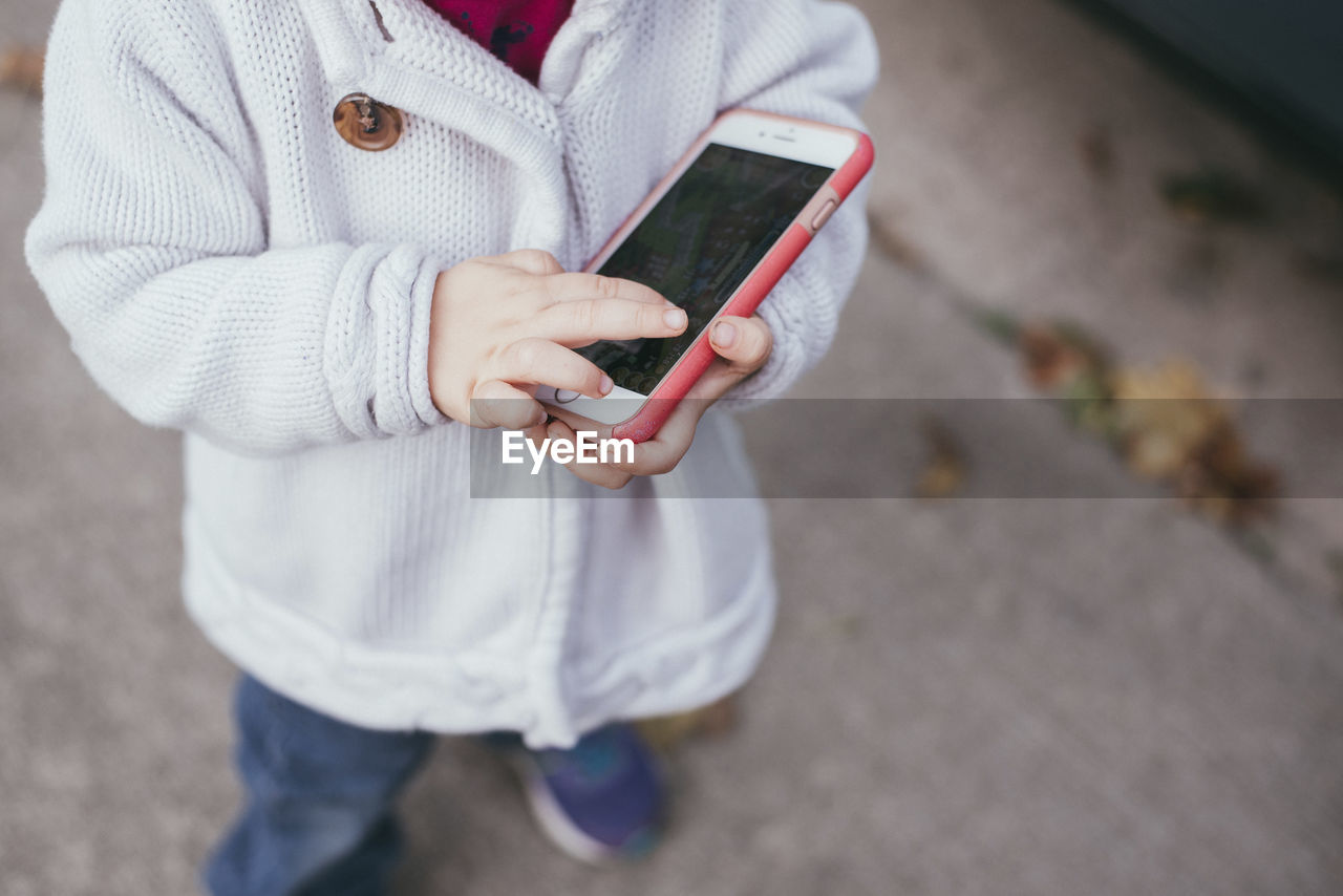 LOW SECTION OF PERSON HOLDING MOBILE PHONE