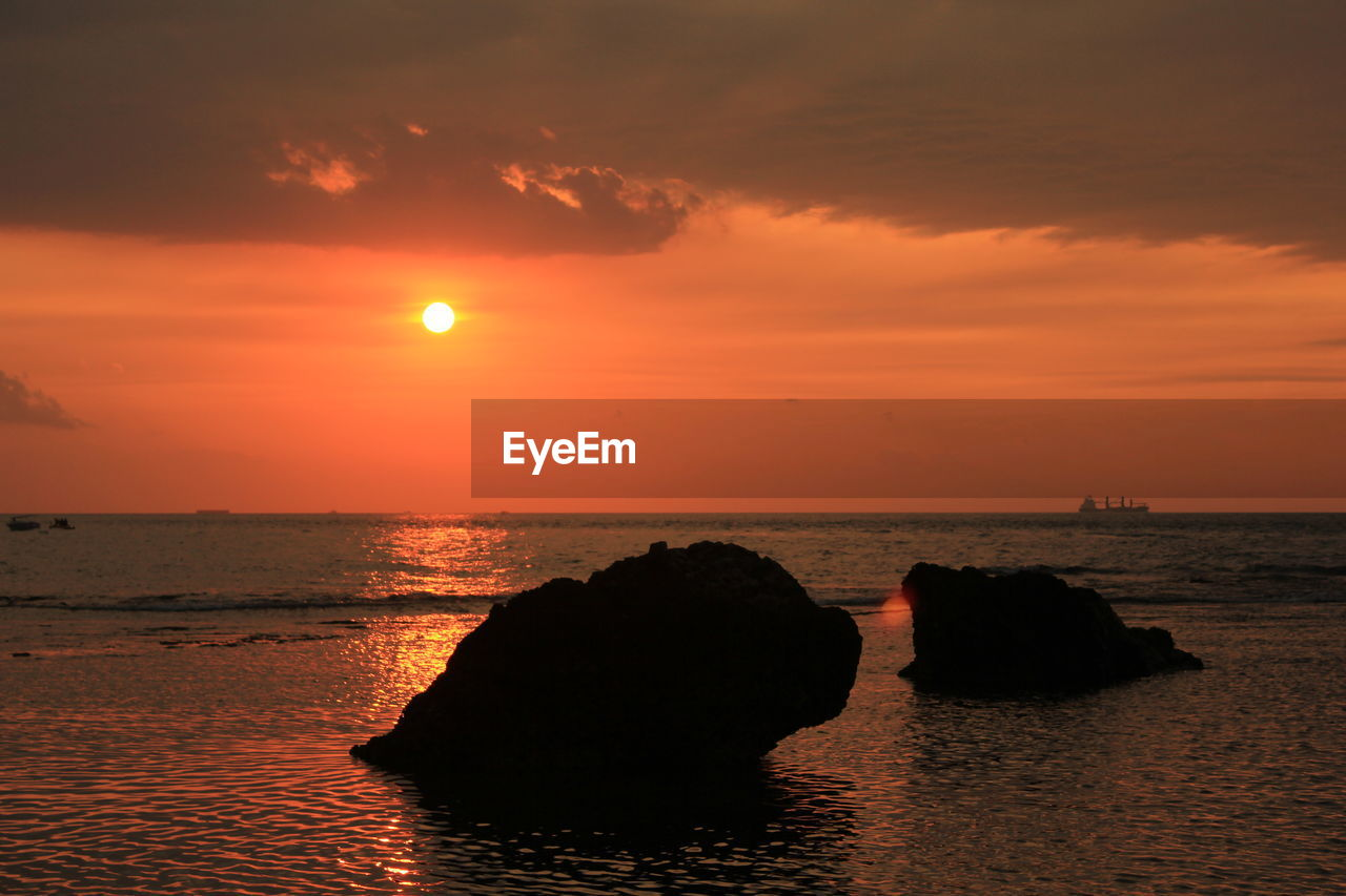 sky, sunset, water, scenics - nature, sea, beauty in nature, tranquility, orange color, tranquil scene, rock, cloud - sky, sun, solid, horizon over water, rock - object, horizon, waterfront, silhouette, no people, outdoors, stack rock