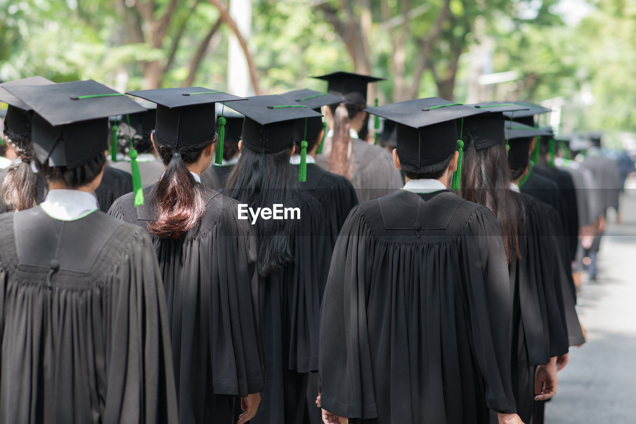 Rear view of students wearing graduation gowns while standing outdoors