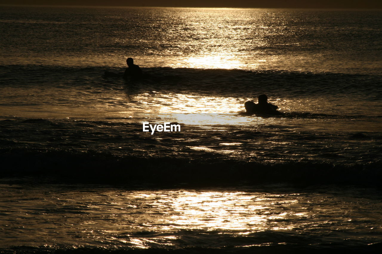 water, silhouette, sunset, sea, beauty in nature, waterfront, nature, scenics, real people, leisure activity, reflection, nautical vessel, tranquility, outdoors, transportation, adventure, men, one person, lifestyles, horizon over water, wave, skill, vacations, sky, extreme sports, paddleboarding, jet boat, day, people