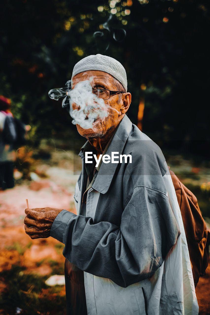 Man exhaling smoke while standing outdoors