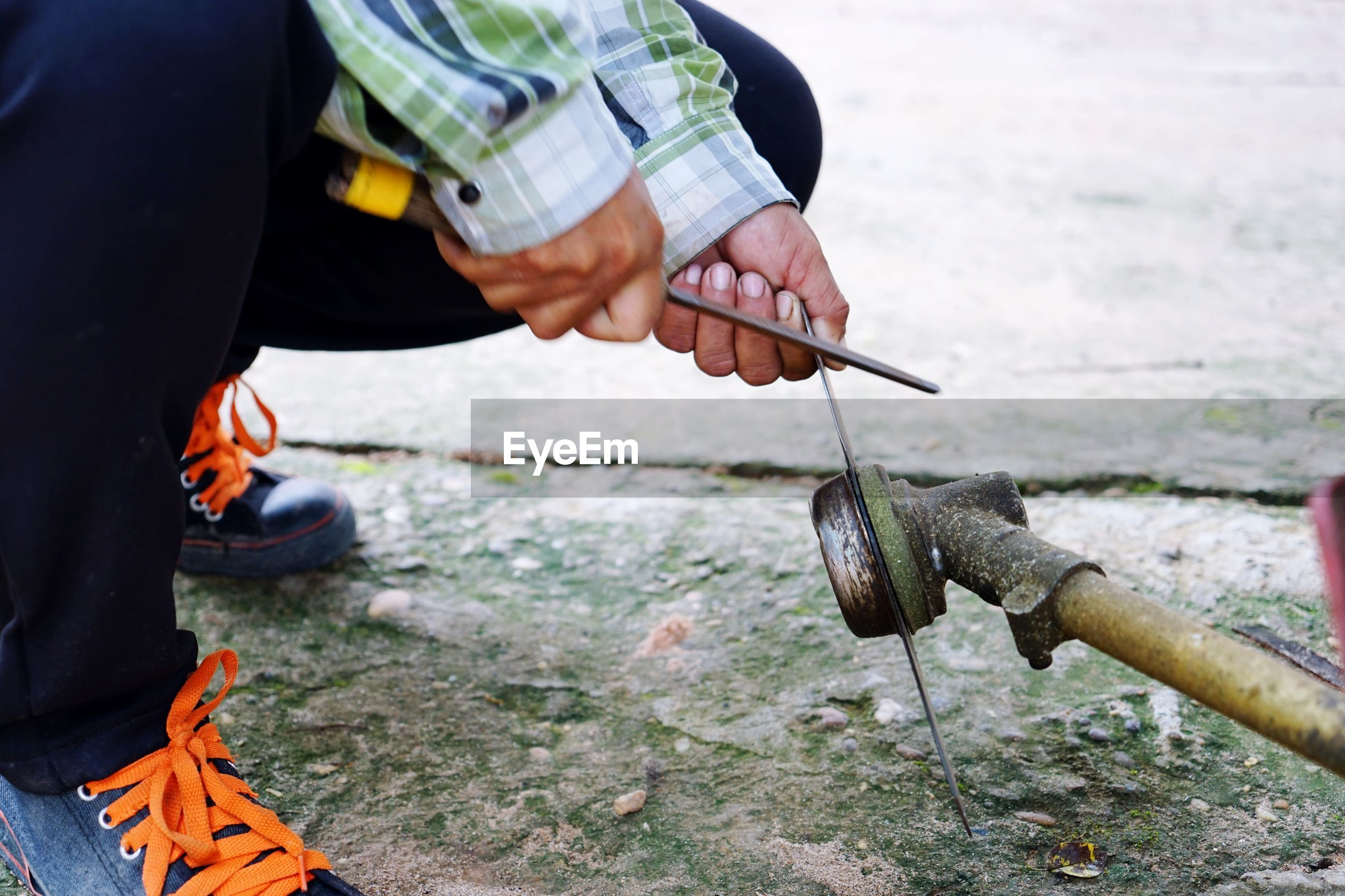 Low section of man cutting water pipe