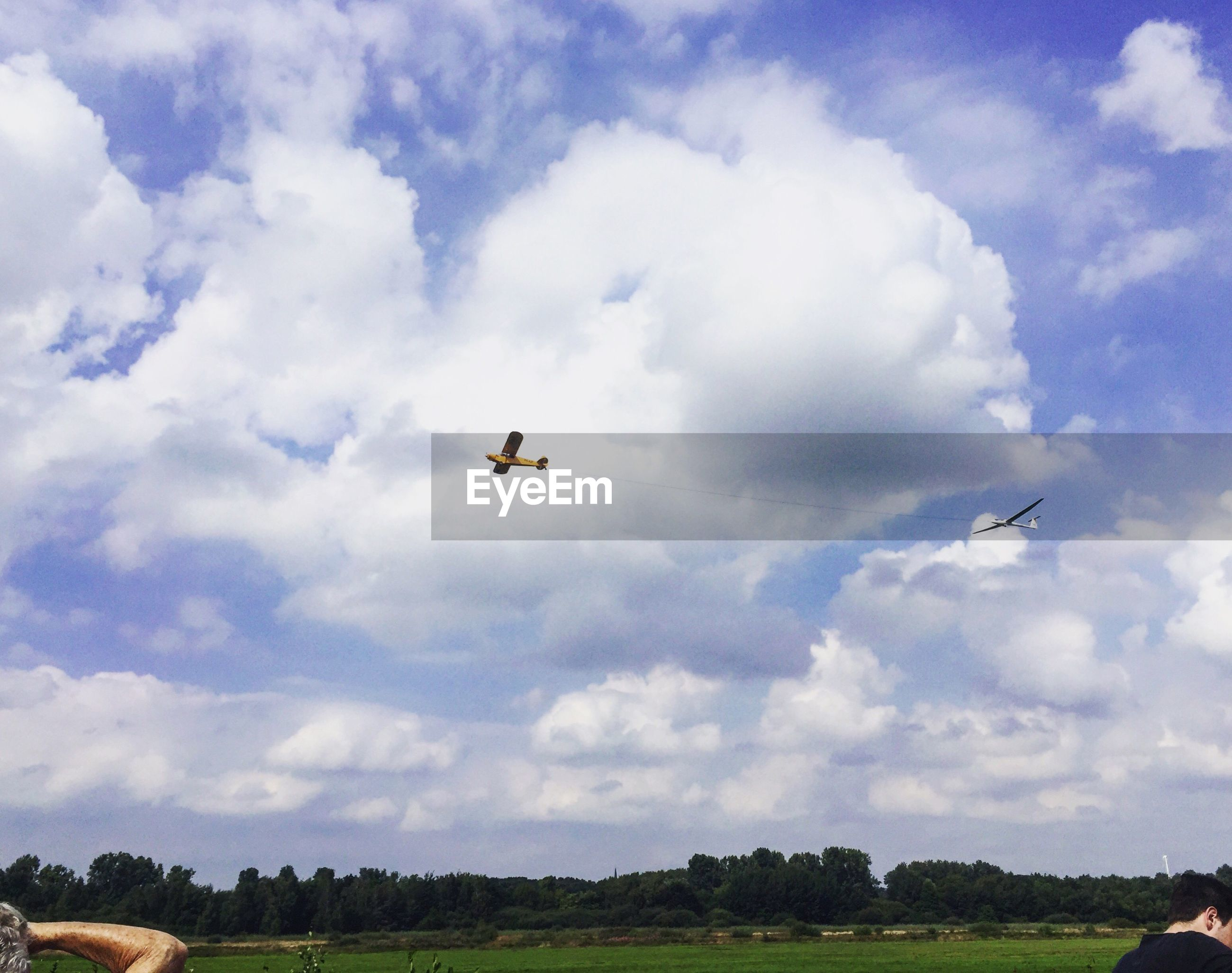 flying, sky, cloud - sky, transportation, mode of transport, bird, low angle view, mid-air, airplane, cloud, cloudscape, air vehicle, cloudy, day, cumulus cloud, nature, blue, scenics, outdoors, flight, beauty in nature, tranquil scene, tranquility, storm cloud, atmospheric mood, dramatic sky, non-urban scene, no people