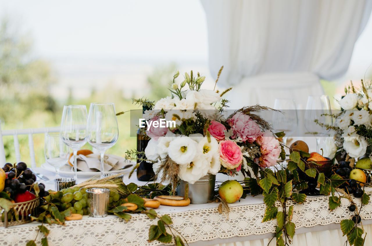 flower, flowering plant, plant, nature, flower arrangement, freshness, celebration, bouquet, glass, decoration, event, wedding, table, focus on foreground, life events, beauty in nature, vulnerability, arrangement, day, fragility, flower head, no people, wedding ceremony, outdoors, setting