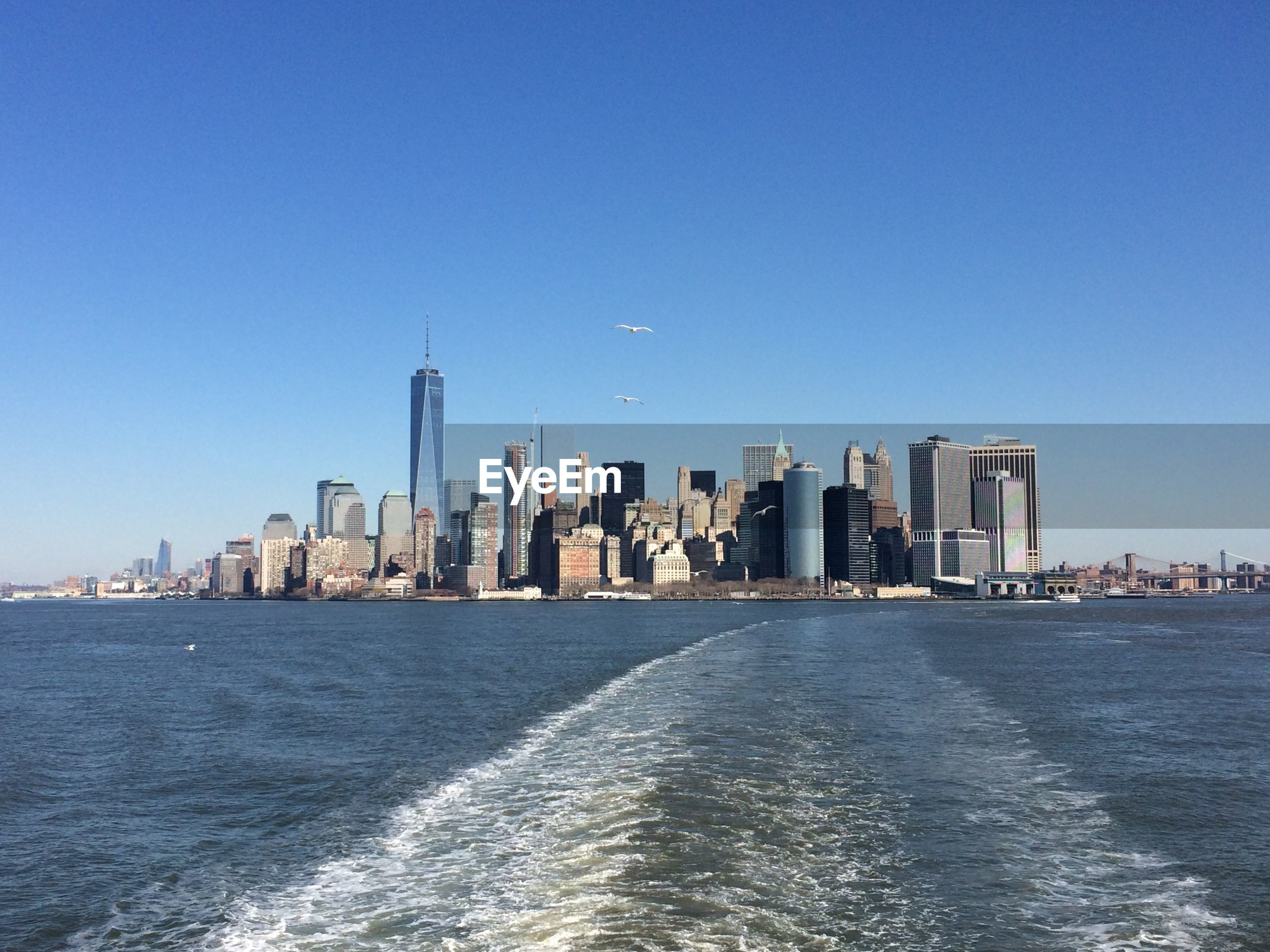 One world trade center by east river against clear blue sky at manhattan