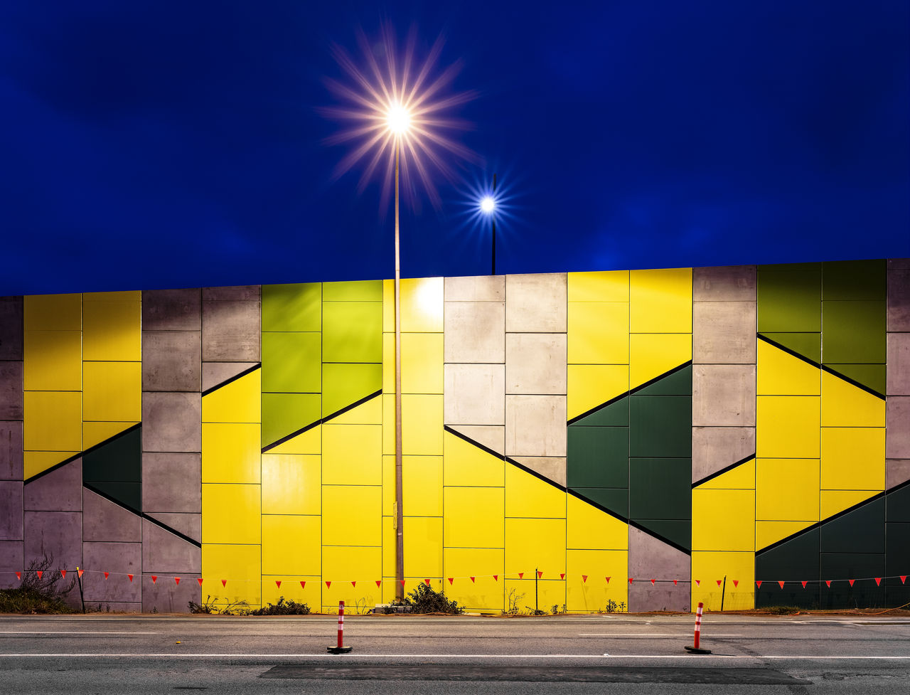 architecture, built structure, street, sky, yellow, city, road, building exterior, transportation, nature, illuminated, outdoors, real people, incidental people, street light, lighting equipment, direction, wall - building feature, multi colored