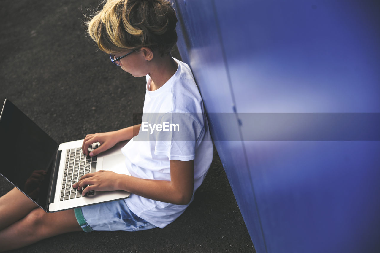 High angle view of boy using laptop while sitting by wall indoors