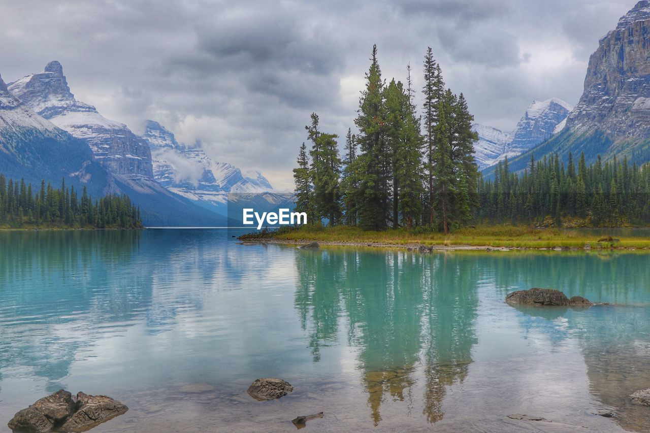 water, beauty in nature, scenics - nature, mountain, tranquil scene, tree, cloud - sky, tranquility, sky, lake, reflection, plant, idyllic, non-urban scene, mountain range, nature, day, waterfront, no people, outdoors, snowcapped mountain, formation, turquoise colored, reflection lake