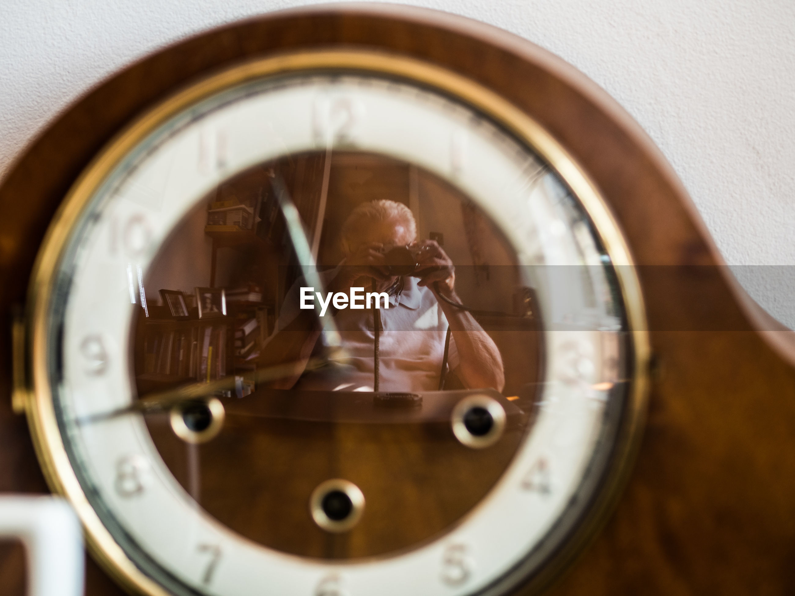 Senior man photographing with camera seen in clock at home