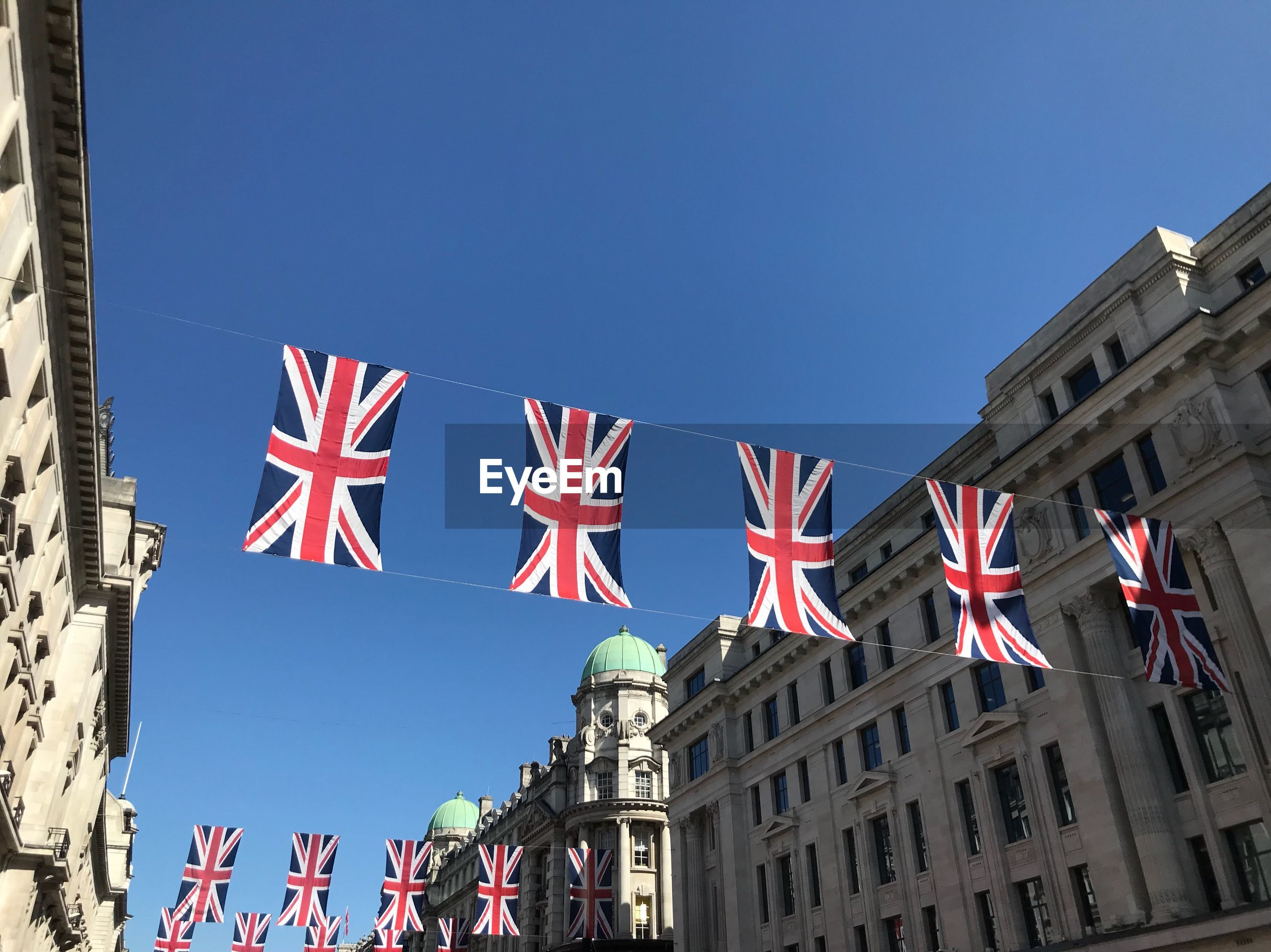 Low angle view of union jacks hanging in city against clear blue sky