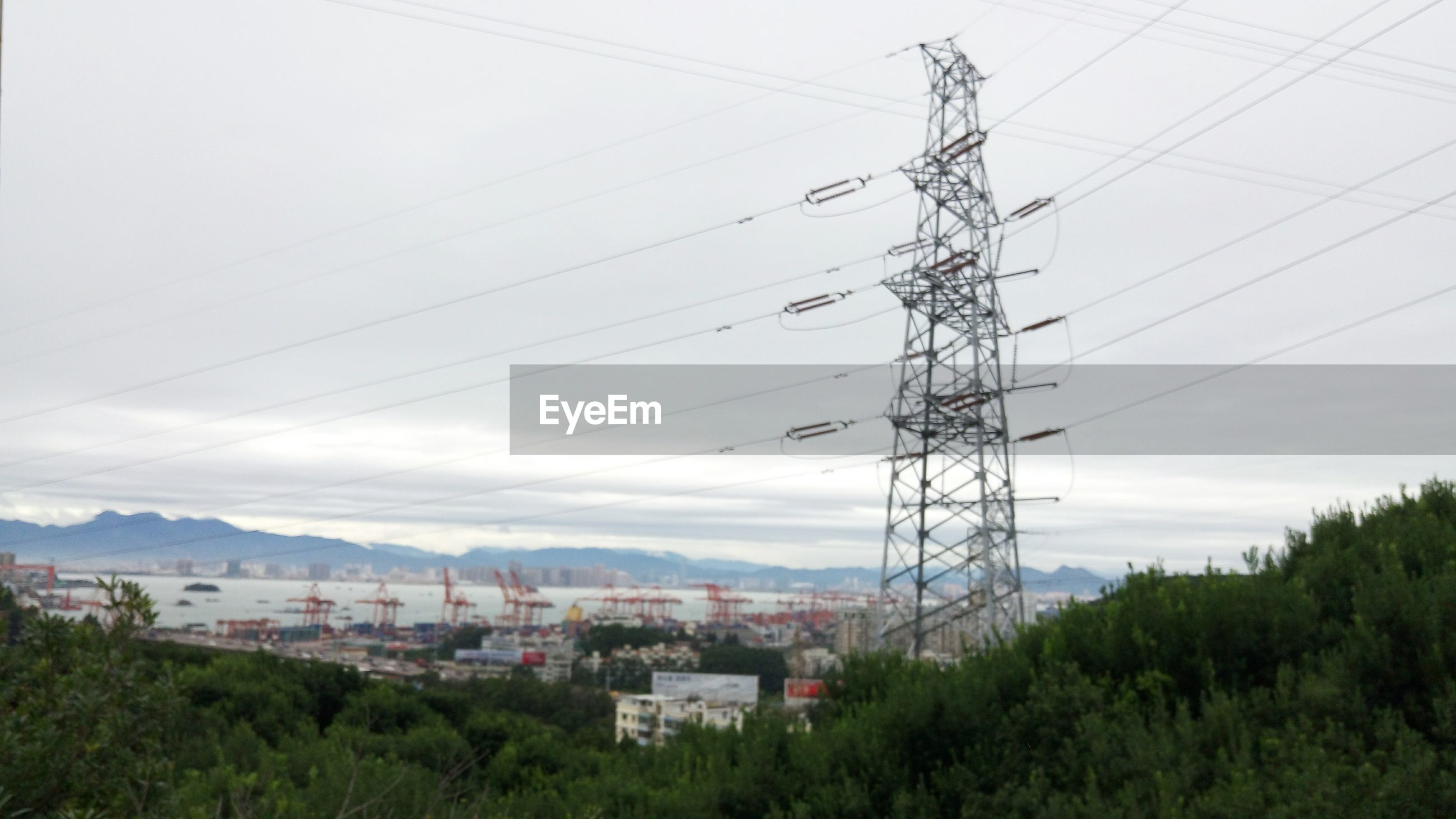 power line, electricity pylon, electricity, power supply, cable, building exterior, sky, tree, built structure, fuel and power generation, connection, architecture, house, technology, residential structure, power cable, town, mountain, residential building, day