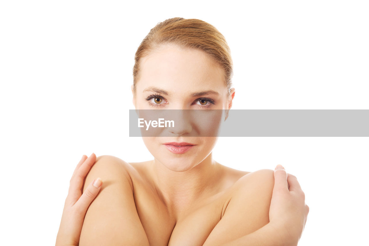 Portrait of topless young woman sitting against white background