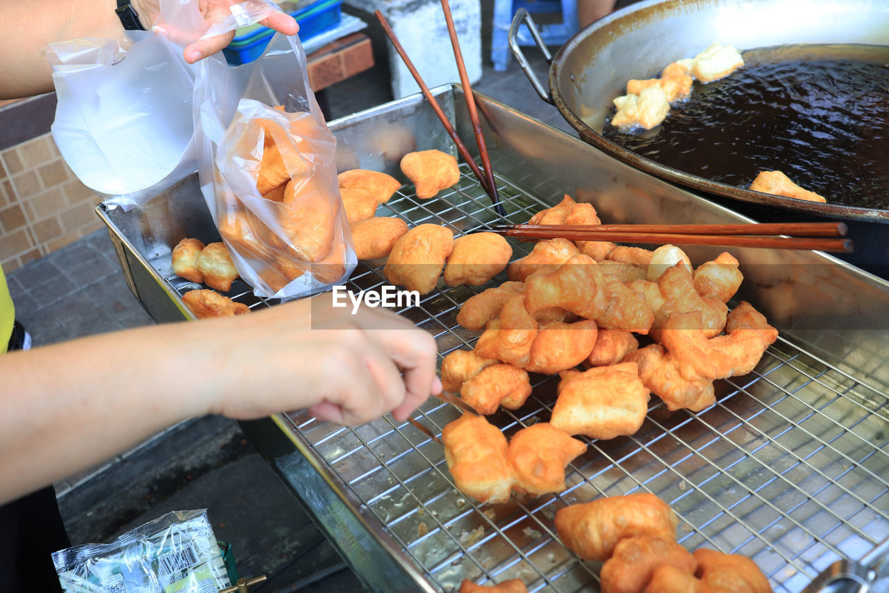 food, food and drink, human hand, meat, hand, freshness, barbecue, preparation, real people, one person, human body part, preparing food, heat - temperature, barbecue grill, holding, men, day, high angle view, retail, outdoors, street food, finger, human limb