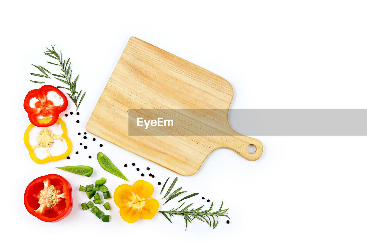 Close-up of cutting board with ingredients over white background