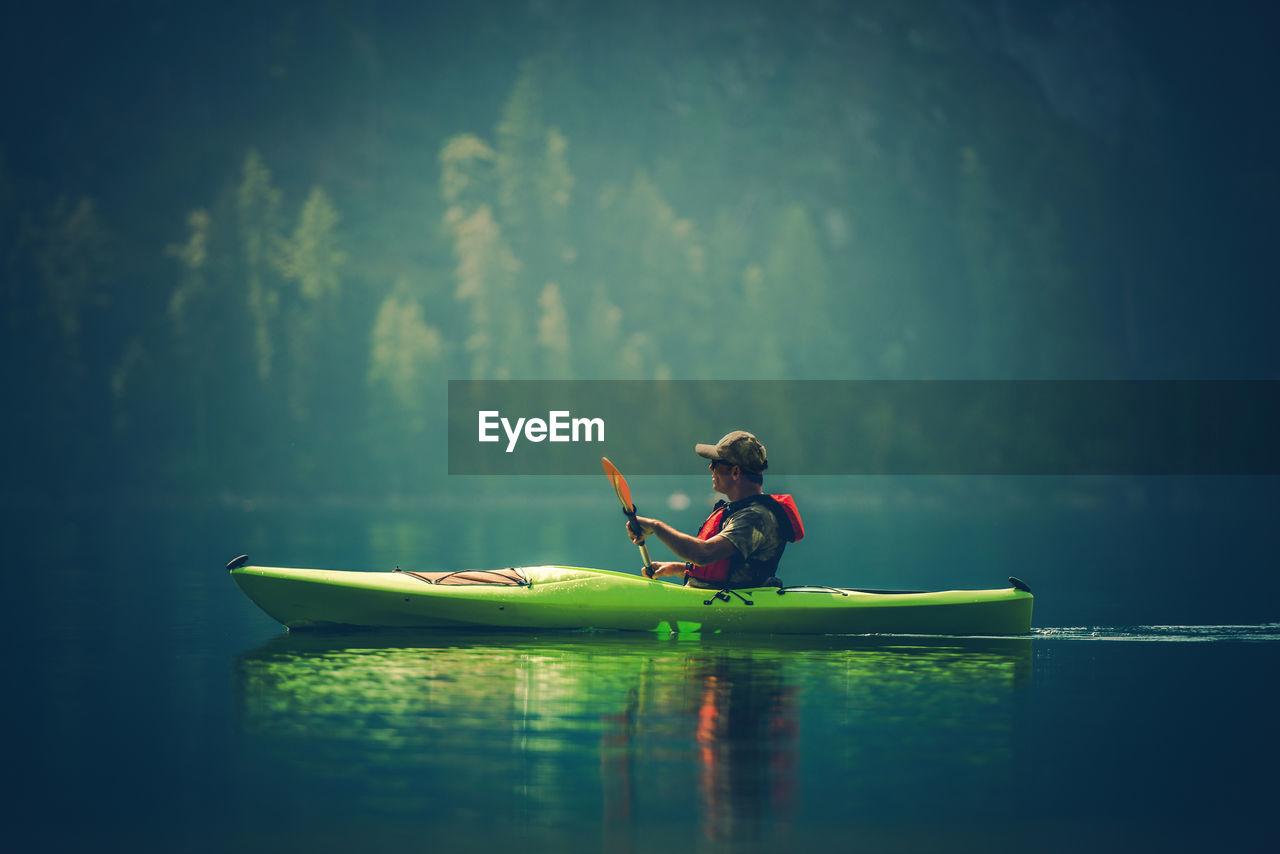Side View Of Man Kayaking In Lake