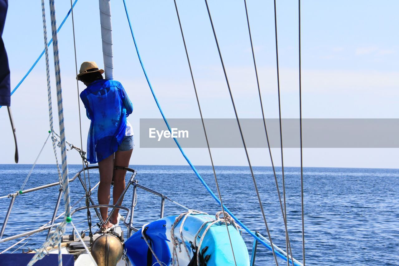 Rear view of woman standing on boat in sea against sky
