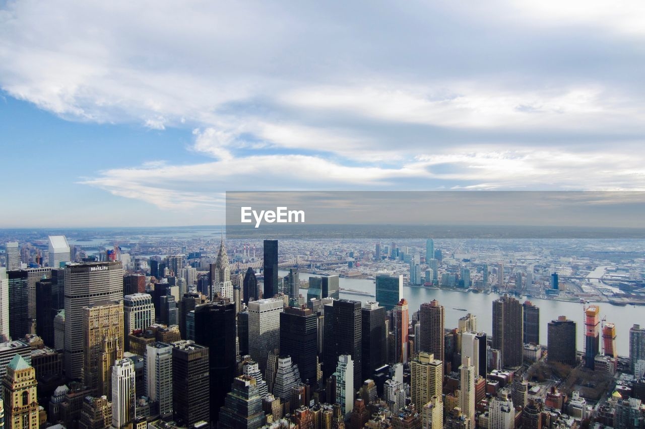 High angle view of cityscape against cloudy sky