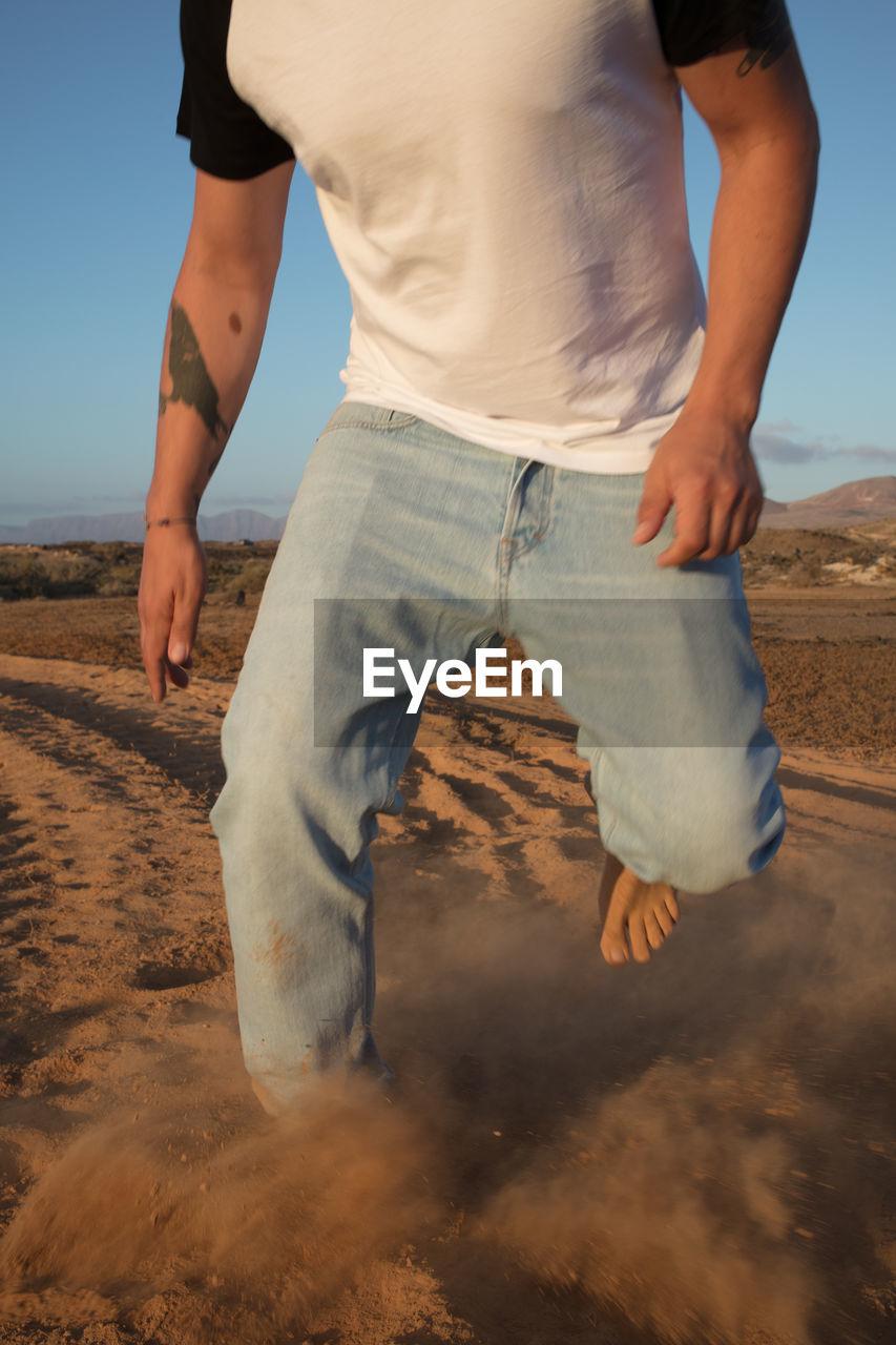 Low section of man running on desert