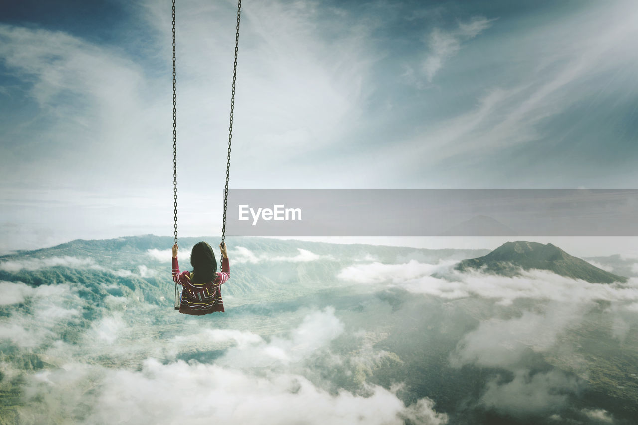 Woman Swinging Over Cloudscape Against Sky