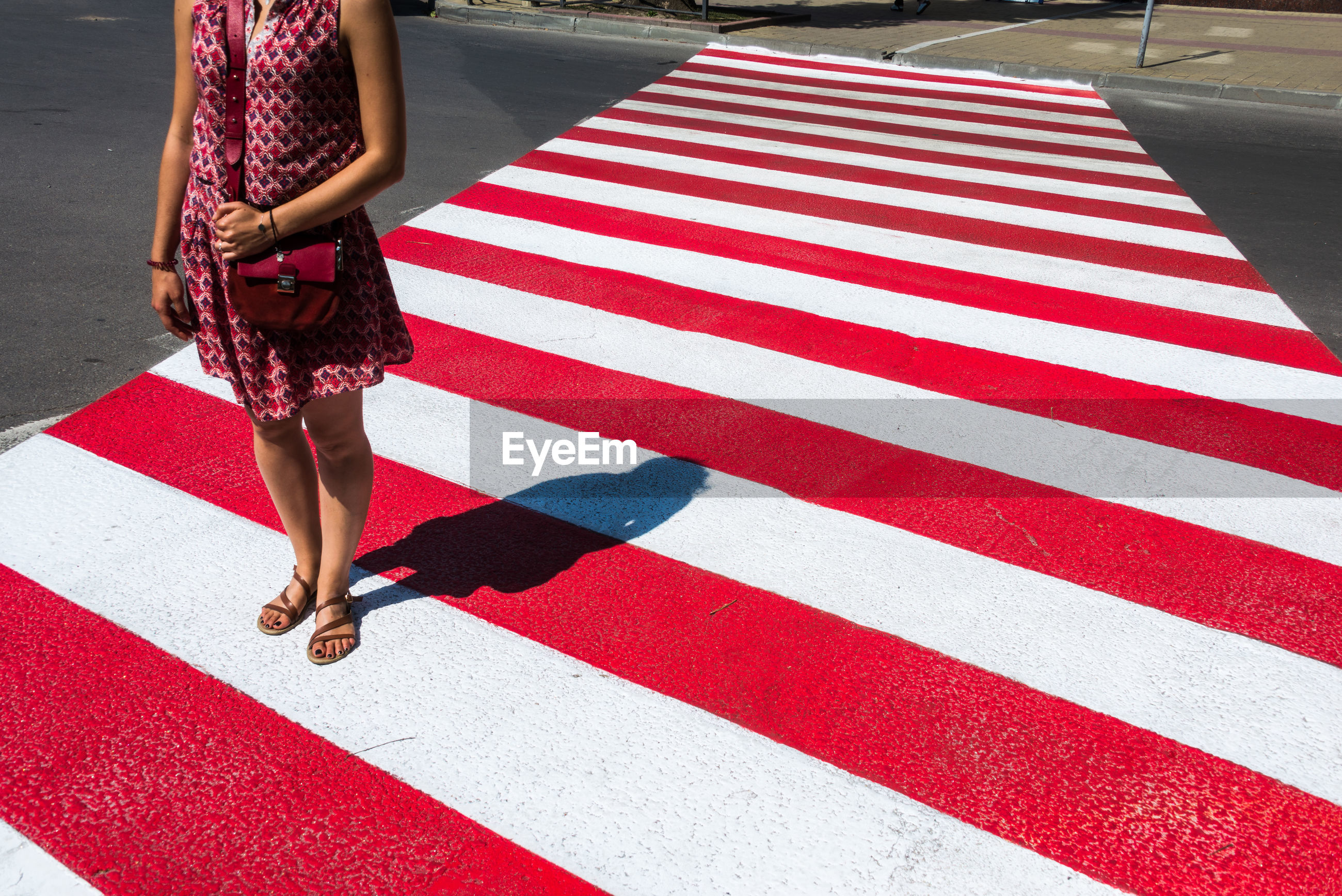 Low section of woman standing on zebra crossing during sunny day