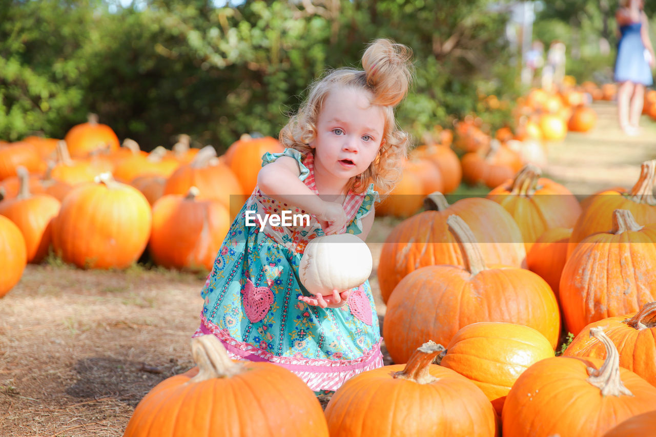 Portrait Of Girl Holding Pumpkin At Park During Autumn