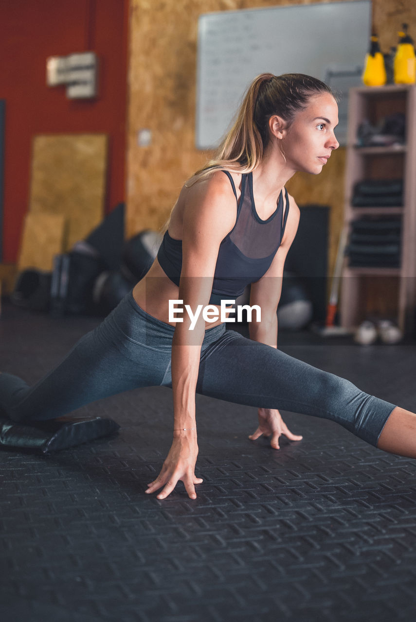 exercising, healthy lifestyle, lifestyles, young women, full length, real people, one person, strength, gym, wellbeing, young adult, sports clothing, balance, sport, leisure activity, concentration, flexibility, indoors, women, health club, physical activity, exercise equipment, blond hair, day, architecture, adult, people