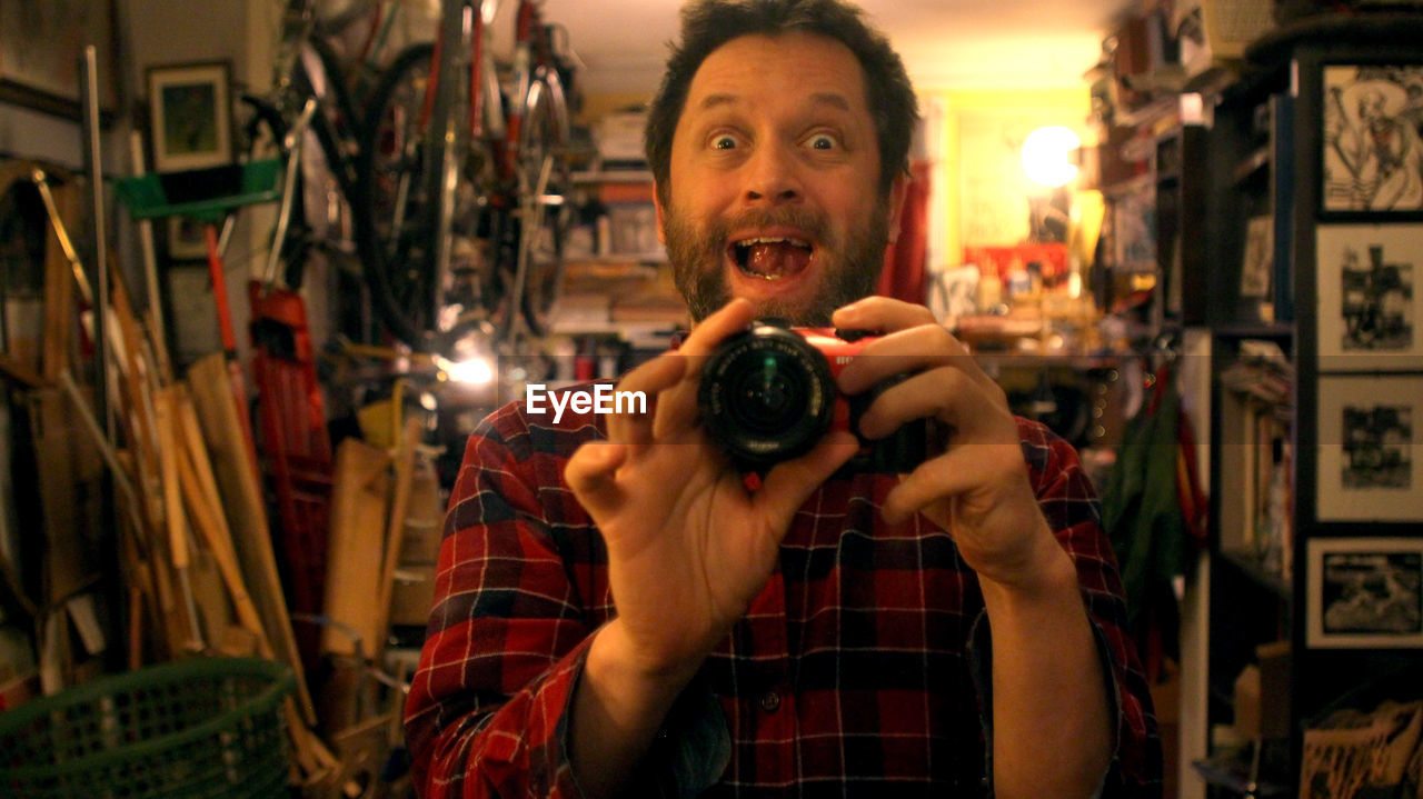 Portrait of surprised man photographing with digital camera in store
